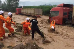 """大暴雨冲走数十辆卡车  司机""""骑绳过河""""惊险获救"""